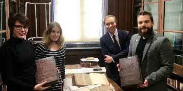 Слева направо Лия Тетер, Лора Чухан Кэмпбелл, Майкл Ричардсон и Бенджамин Пол с книгами в комнате редких книг Центральной библиотеки Бристоля Университет Бристоля